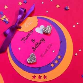 Faire-part rond aux couleurs acidulées orange, violet et rose fuchsia avec coeurs, ruban et étoiles et nuage